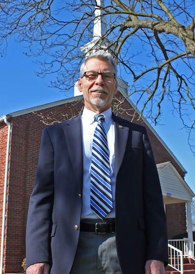 Dr. Kenneth Startup standing in front of chapel